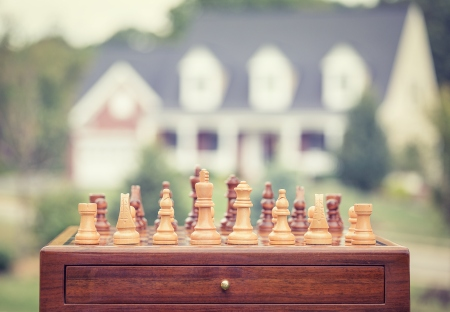 Buying real estate strategy chess game with house background