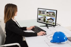 Young Female Architect Looking At Designs Of House On Computer In Office