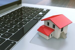Small house on laptop keyboard. Real estate agency online. Concept. 3d illustration